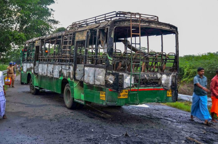 A man walks past a vandalised government bus during a violent protest against the closure of Vedanta's Sterlite Copper unit, in Tuticorin, on Friday. PTI