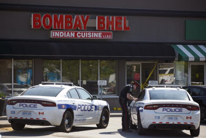 Police stand watch at the scene of an explosion at a restaurant in Mississauga, Ontario, on Friday, May 25, 2018. An explosion caused by a homemade bomb ripped through an Indian restaurant where children were present for family parties at a mall in the To