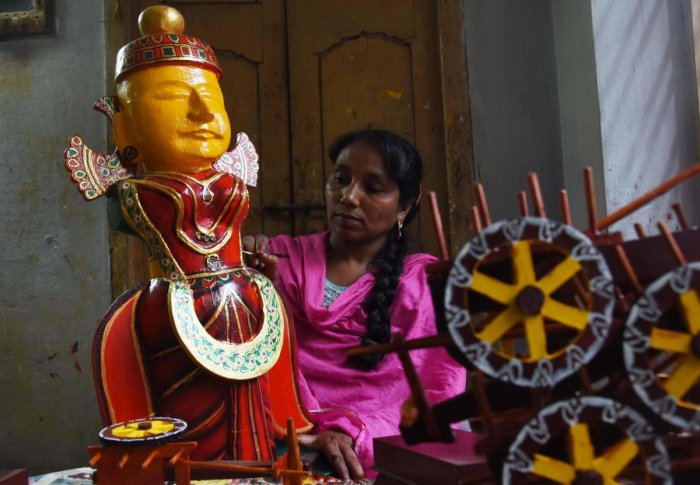 A girl busy gives final touches to a toy in Kondapalli. AFP