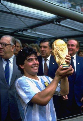 Diego Maradona holds aloft the 1986 FIFA World Cup trophy.