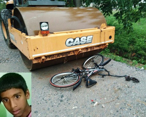 The road-roller that crushed Manu R (inset) at Thalaghattapura Layout in Hemmigepura on Friday. His bicycle is seen lying on the road.