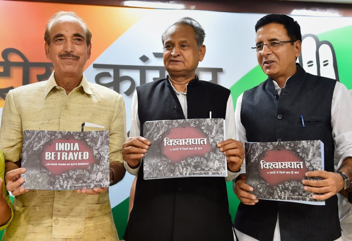 """Gehlot, AICC National Spokesperson Randeep Singh Surjewala and All India Mahila Congress President Sushmita Dev release a booklet """"India Betrayes ... In Four Years of BJP's Misrule"""" during a press conference, in New Delhi on Saturday. PTI"""