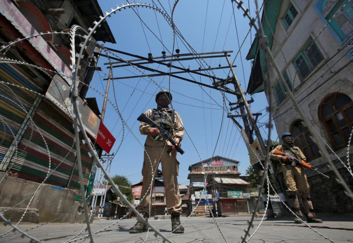 Indian policemen stand guard behind concertina wire during a strike called by separatists to mark the death anniversaries of chief cleric of Kashmir, Moulana Mohammad Farooq and Abdul Gani Lone, a Kashmiri separatist leader, in Srinagar May 21, 2018. REUTERS/Danish Ismail