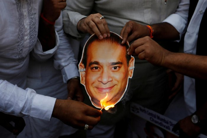 Youth Congress workers burn a cut-out with an image of billionaire jeweller Nirav Modi during a protest in Mumbai. REUTERS