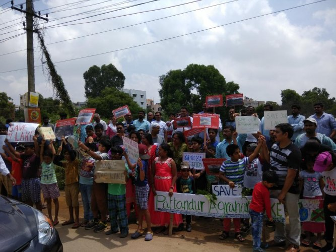 Residents form a human chain seeking the authorities to protect the Pattandur Agrahara Lake, on Sunday.