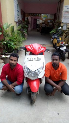 The suspects and the scooter allegedly used in the crime.