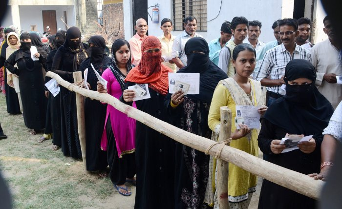 Burqa-clad women, along with other voters, show their voter identity cards as they wait to cast thier votes for Noorpur Assembly bypolls, in Bijnor, on Monday. PTI