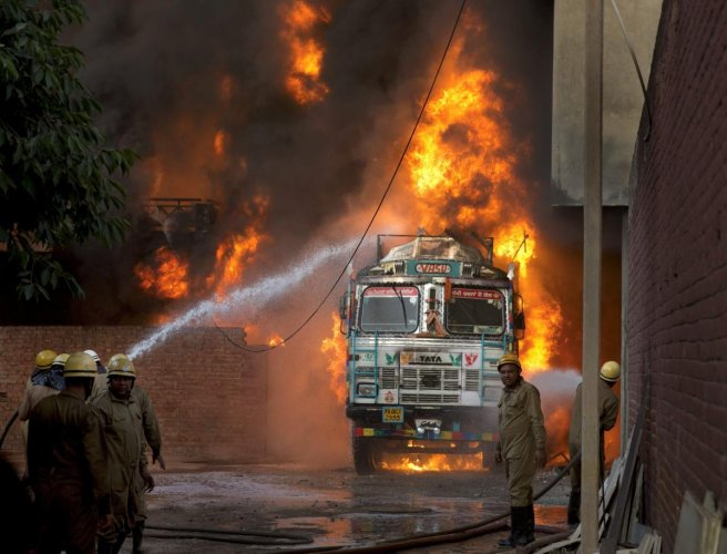 Firefighters douse flames on a truck which caught fire at Malviya Nagar in New Delhi, on Tuesday, May 29, 2018. The truck fire later spread to a nearby godown. PTI Photo