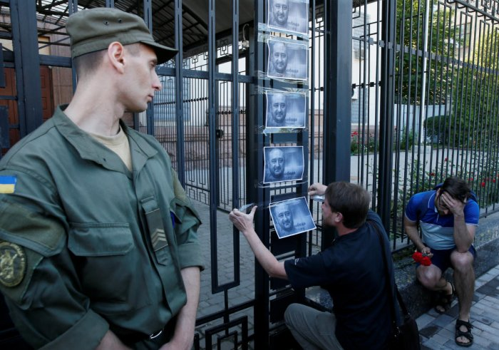 A man hangs a picture of Russian dissident journalist Arkady Babchenko, who was shot dead in the Ukrainian capital on May 29, on a fence of the Russian embassy in Kiev, Ukraine May 30, 2018. REUTERS Photo