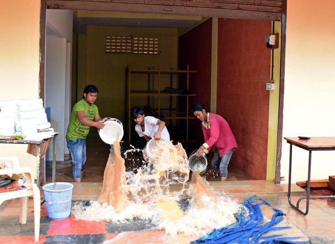 Rain water logged inside the Hardware shop near Mahesh College, Kottara Chowki due to heavy rainfall yesterday in Mangaluru. Workers trying to clear the rain water which is logged inside the shop. DH Photo.