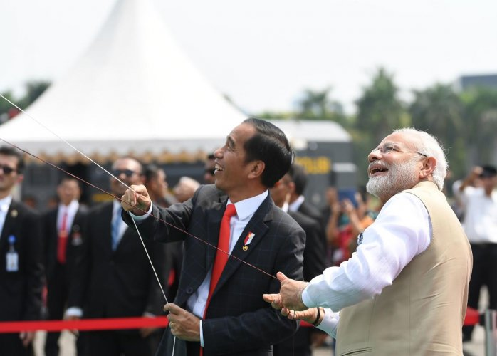 This handout photograph taken and released by India's Press Information Bureau (PIB) on May 30, 2018 shows Indian Prime Minister Narendra Modi (R) and Indonesian President Joko Widodo (C) laugh as they fly kites at the India-Indonesia Kite Exhibition in J