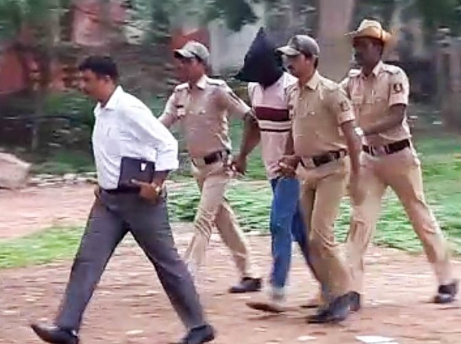 Officials of the Special Investigation Team escort one of the accused in the Gauri Lankesh murder case.
