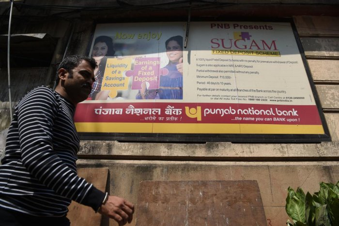 A man walks past a sign for Punjab National Bank in Mumbai. AFP
