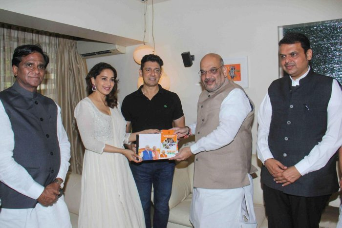 BJP president Amit Shah along with Maharashtra Chief Minister Devendra Fadnavis meets Bollywood actress Madhuri Dixit at her Juhu residence as a part of his 'Sampark Se Samarthan' campaign, in Mumbai on Wednesday. PTI