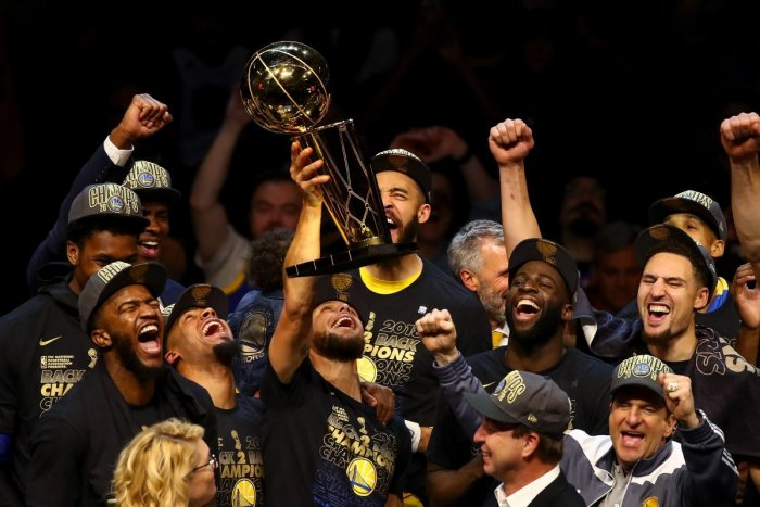 Golden State Warriors celebrate with the Larry O'Brien Trophy after defeating the Cleveland Cavaliers in Game Four of the 2018 NBA Finals on Friday. AFP