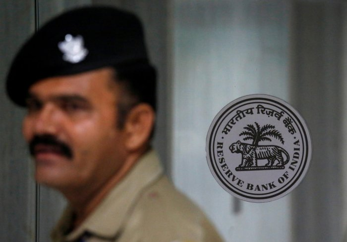 FILE PHOTO: A security guard stands next to the logo of Reserve Bank of India (RBI) inside its headquarters in Mumbai, India, June 6, 2018. REUTERS