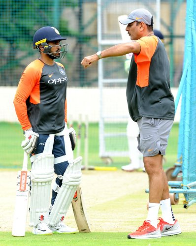WORDS OF WISDOM Karun Nair (left) gets some advice from coach Ravi Shastri during a training session on Monday. DH PHOTO/ SRIKANTA SHARMA R