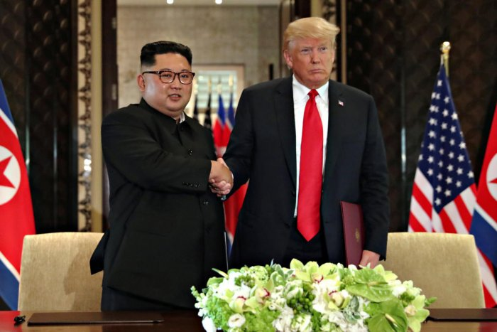 U S President Donald Trump shakes hands with North Korea's leader Kim Jong Un after they signed documents that acknowledged the progress of the talks and pledge to keep momentum going, after their summit at the Capella Hotel on Sentosa island in Singapore