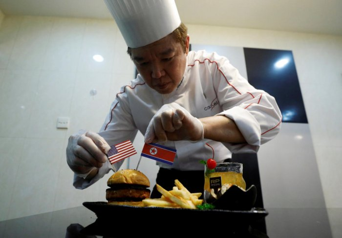 Chef Abraham Tan of Royal Plaza on Scotts' Carousel restaurant puts finishing touches to his creation, the Trump Kim burger, in Singapore. Reuters photo.
