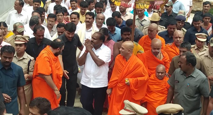 Chief Minister H D Kumaraswamy greets his supporters after participating in a special puja at Adichunchanagiri Mutt in Nagamangala taluk, Mandya district, on Wednesday. Seer Nirmalanandanatha Swami is seen. DH Photo