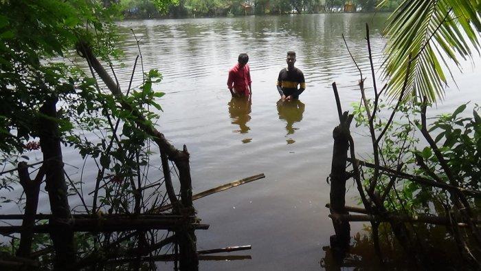 Two youths stand in waist-deep water at Kharviwada village of Ankola taluk, Uttara Kannada district. dh photo