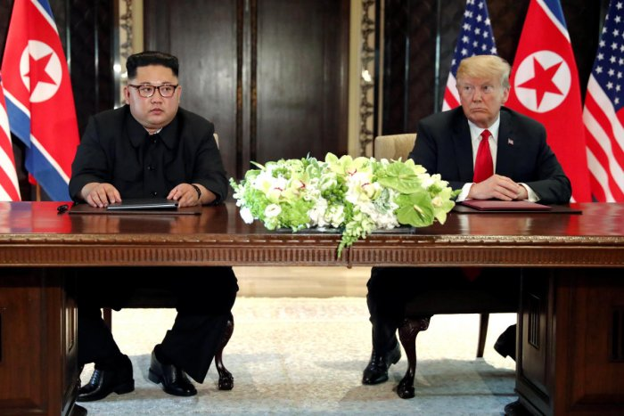 US President Donald Trump and North Korea's leader Kim Jong Un hold a signing ceremony at the conclusion of their summit at the Capella Hotel on the resort island of Sentosa, Singapore. Reuters photo.