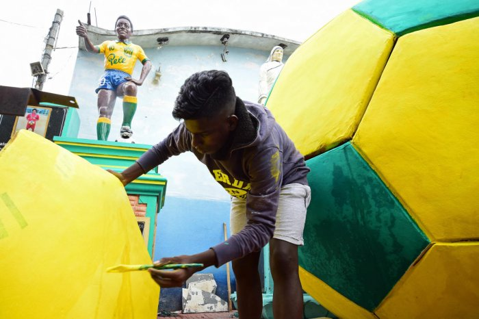 A football fan in Gowthampura gives finishing touches to the settings in the neighbourhood ahead of the World Cup on Wednesday. DH Photo