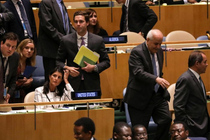 Palestinian Ambassador to the United Nations Riyad Mansour (2nd from R) passes U S Ambassador Nikki Haley (seated L) during a vote on the adoption of a draft resolution by the United Nations General Assembly to deplore the use of excessive force by Israel