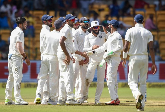 Umesh Yadav with teammates celebrates the wicket of Afghanistan batsman Mohammad Nabi during the second day of a one-off test match, at M Chinnaswamy Stadium, in Bengaluru on Friday, June 15, 2018. PTI Photo