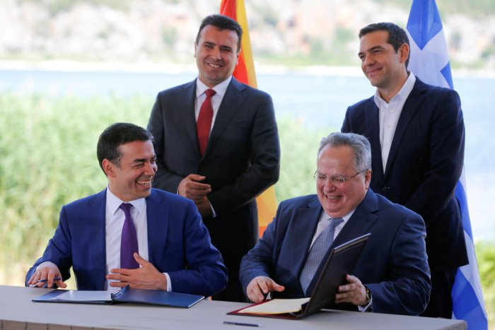 Greek Foreign Minister Nikos Kotzias and his Macedonian counterpart Nikola Dimitrov sign an accord to settle a long dispute over the former Yugoslav republic's name as Greek Prime Minister Alexis Tsipras and Macedonian Prime Minister Zoran Zaev look on in the village of Psarades, in Prespes, Greece, June 17, 2018. Reuters