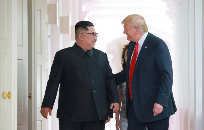 In this picture taken on June 12, 2018 and released from North Korea's official Korean Central News Agency (KCNA) on June 13, 2018, US President Donald Trump (R) and North Korea's leader Kim Jong Un (L) walk to attend their historic US-North Korea summit,