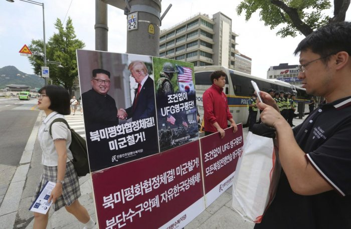 A man takes pictures of a photo showing US President Donald Trump and North Korean leader Kim Jong Un as a member of People's Democratic Party stands to oppose military exercises between the United States and South Korea near the US embassy in Seoul, South Korea.