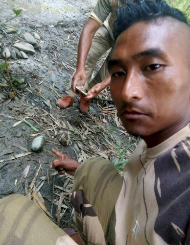 A security person shows an unexploded grenade at the site of an ambush by suspected NSCN-K on Assam Riffle personnel, at Aboi in Mon district of Nagaland on Sunday, June 17, 2018. At least four Assam Rifles personnel were killed in the ambush. (PTI Photo)
