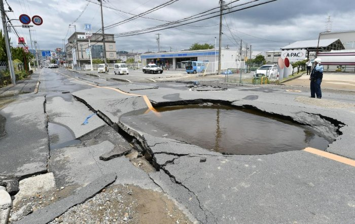 A crack is filled with water on a road after water pipes were broken following an earthquake in Takatsuki city, Osaka, western Japan, Monday. (AP/PTI Photo)