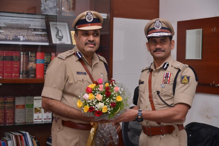 Outgoing City Police Commissioner Vipul Kumar (right) greets T R Suresh, who took charge as City Police Commissioner in Mangaluru on Monday.