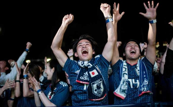 Japanese supporters celebrates Japanese team's goal in the penalty kick while watching Japan's first World Cup match in the Group H against Colombia at a fan zone in Tokyo on June 20, 2018. / AFP PHOTO