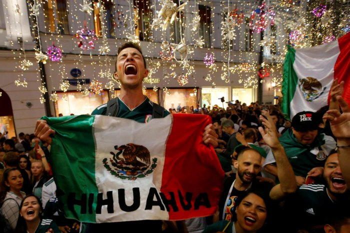Mexico's fans celebrate victory of their team after the match on Sunday. (REUTERS/Sergei Karpukhin)