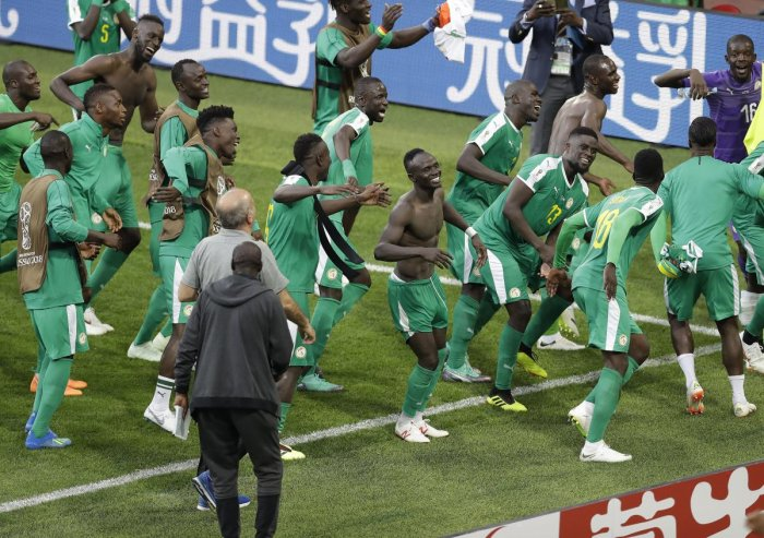 Senegal players celebrate their win over Poland on Tuesday. Senegal became the first African nation to score a win at this World Cup. AP/PTI