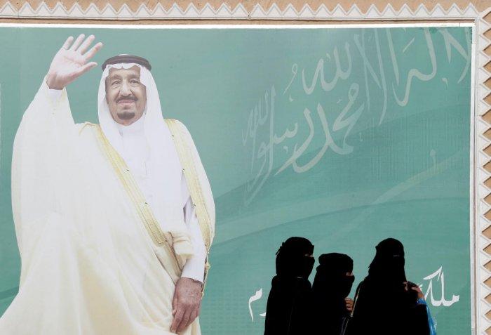 Women walk past a poster of Saudi Arabia's King Salman bin Abdulaziz Al Saud during Janadriyah Cultural Festival on the outskirts of Riyadh, Saudi Arabia. (Reuters file photo)