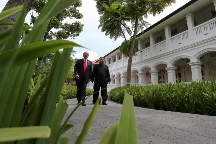 U.S. President Donald Trump and North Korea's leader Kim Jong Un walk together before their working lunch during their summit at the Capella Hotel on the resort island of Sentosa, Singapore June 12, 2018.