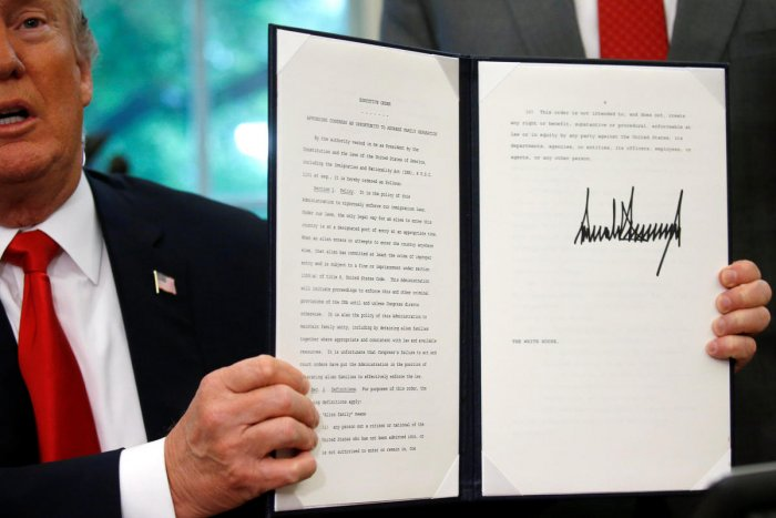 US President Donald Trump displays an executive order on immigration policy after signing it in the Oval Office at the White House in Washington on June 20, 2018. (REUTERS/Leah Millis)