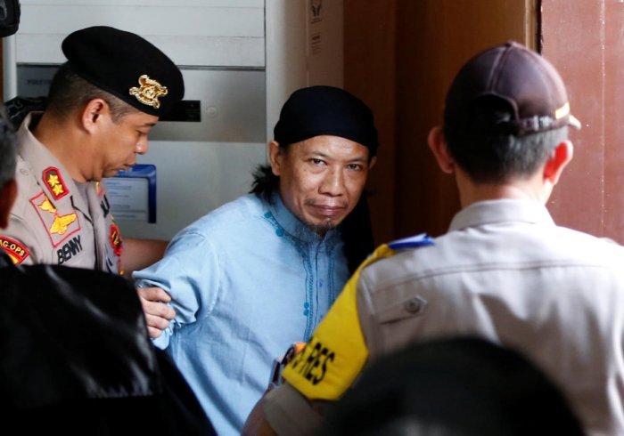 Islamic cleric Aman Abdurrahman leaves a court following his verdict in Jakarta, Indonesia, June 22, 2018. REUTERS