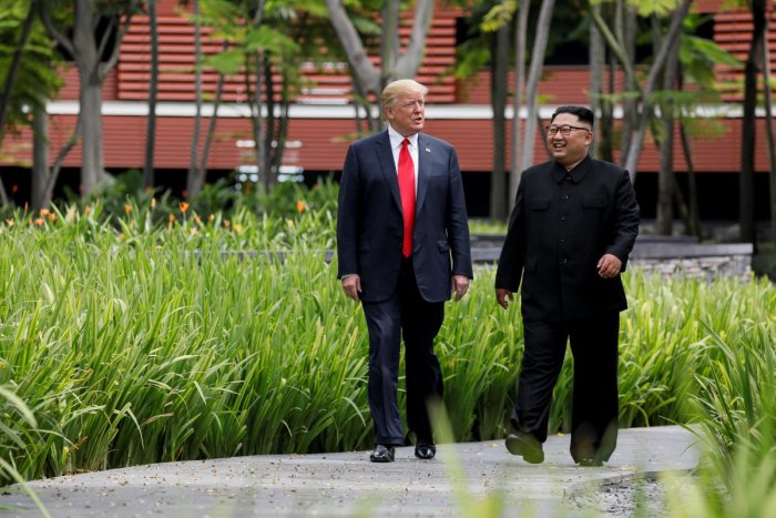 U.S. President Trump and North Korea's Kim walk together before their working lunch during their summit in Singapore. Reuters file photo