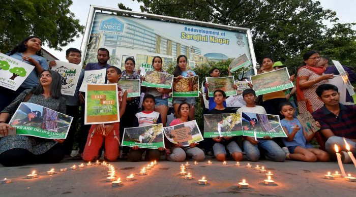 Activists from various environmental organisations during a candle light vigil against cutting of trees in Nauroji Nagar area, in New Delhi. PTI photo.