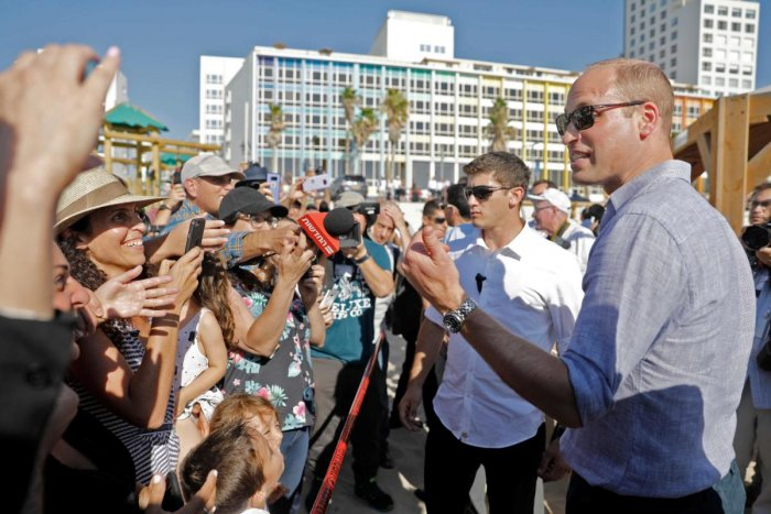 Reporters and beach-goers swarm around Britain's Prince William (right) as he visits a beach in the coastal Israeli Mediterranean city of Tel Aviv on June 26, 2018. AFP