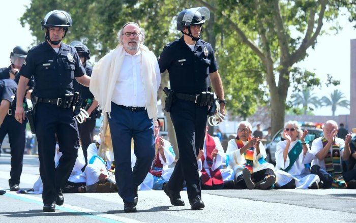 Members of the clergy from different denominations are arrested by police for blocking the road in front of the Federal Building in an act of civil disobedience as they joined activists protesting the visit of Attorney General Jeff Sessions as well as the