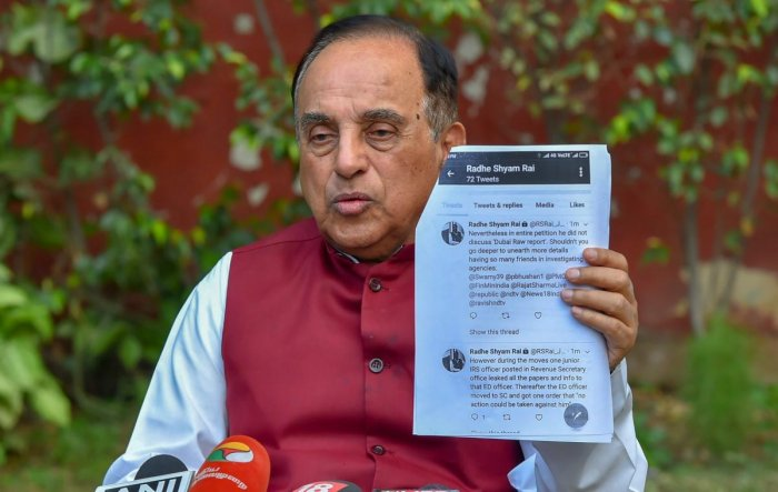Bharatiya Janata Party MP Subramanian Swamy shows a document while addressing a press conference at his residence, in New Delhi on Wednesday. PTI