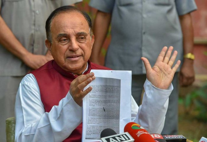 BJP MP Subramanian Swamy shows a document while addressing a press conference at his residence, in New Delhi. PTI Photo