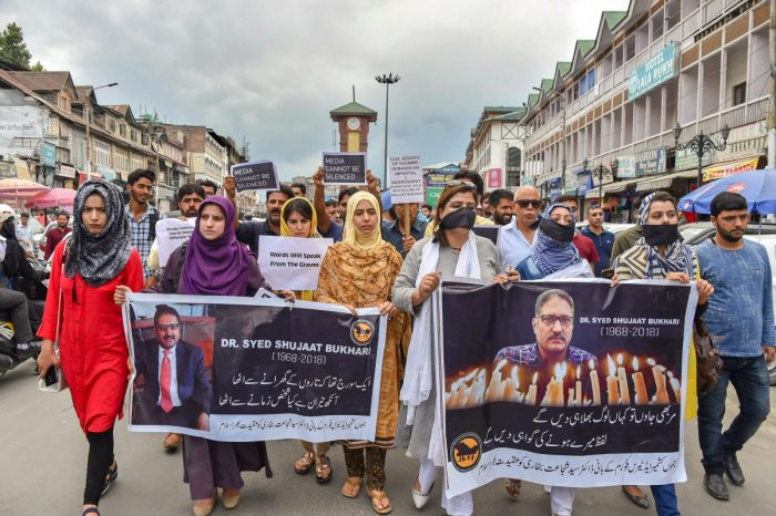 Journalists hold placards during a silent protest march against the killing of Rising Kashmir newspaper editor-in-chief Shujaat Bukhari, in Srinagar on Tuesday, June 26, 2018. PTI Photo