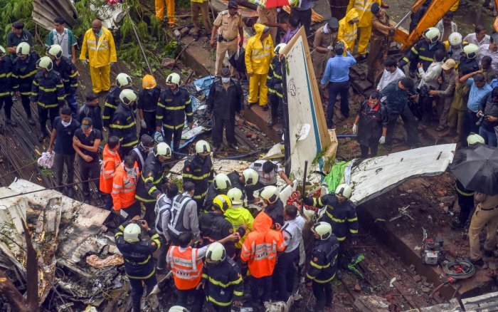 Rescue personnel stand near the debris of the chartered plane that crashed in Ghatkopar's Jivdaya Lane, killing 5, in Mumbai on Thursday, June 28, 2018. PTI Photo